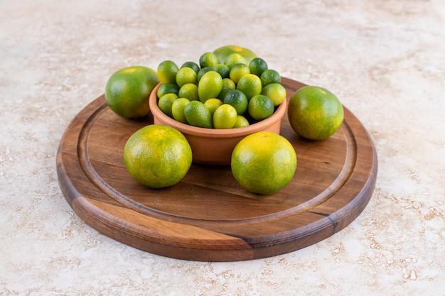 Stapel van mandarijn in kom op een houten bord met mandarijnen.