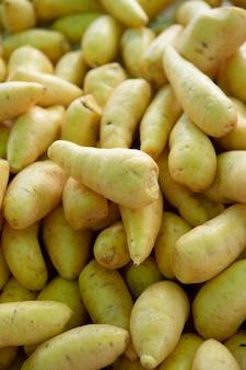 Stapel van mandioquinha-baroa-aardappel bij openluchtmarkt.