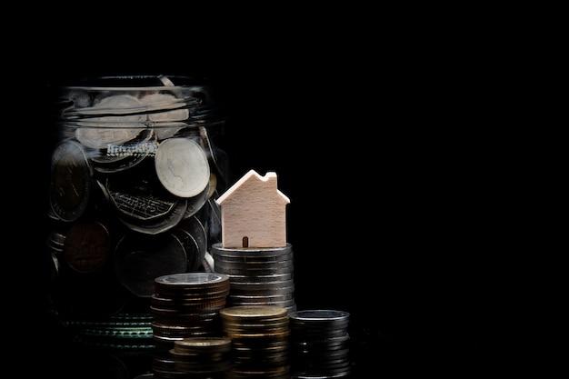 Stapel van munt en duidelijke kruik met muntstuk met houten huis op zwarte achtergrond