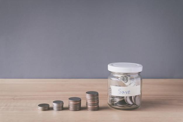 Stapel van munt en muntstuk in een glaskruik op houten bureau, die geldconcept bewaren