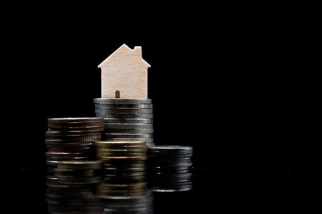 Stapel van munt met houten huis op zwarte achtergrond