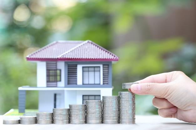Stapel van muntengeld en modelhuis