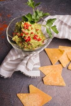 Stapel van nachos dichtbij guacamole in kom en servet