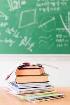 Stapel van notitieboekjes op bureau in klaslokaal