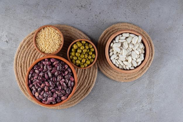 Stapel van ongekookte linzen, bonen en rijst op stenen achtergrond.