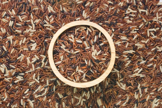 Stapel van ongepelde rijst op kom houten achtergrond