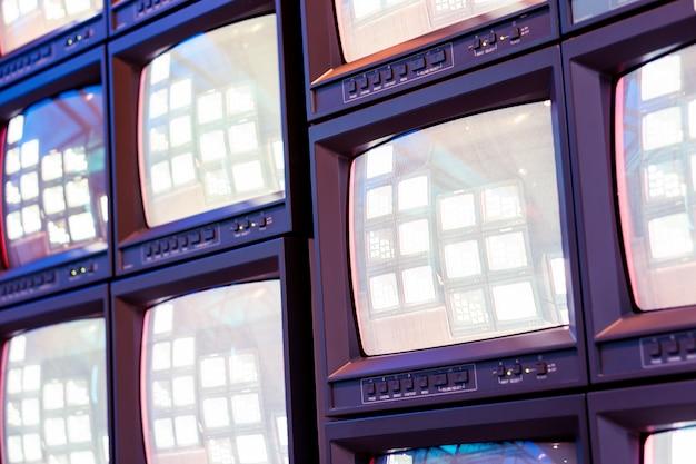 Stapel van oude analoge televisiemonitor met levend signaalprogramma in uitzendstudio