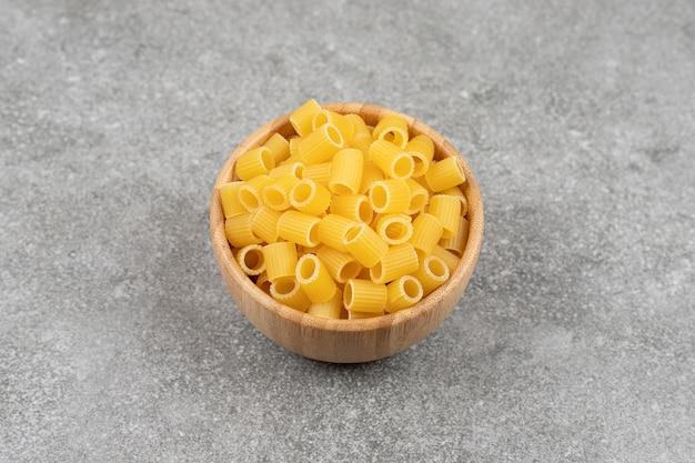 Stapel van rauwe macaroni in houten kom