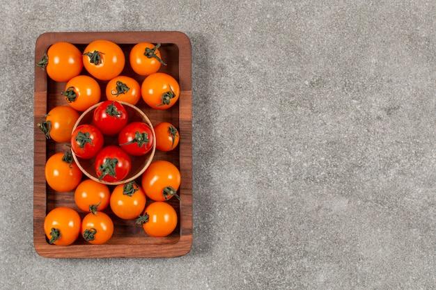 Stapel van rode en gele tomaten op een houten bord.