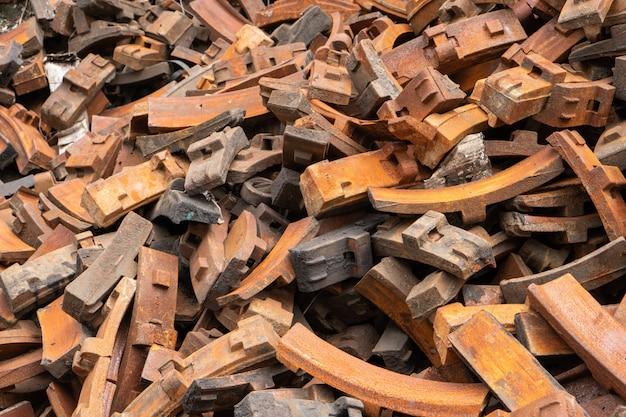 Stapel van roestig staalremblok van locomotief in oude verlaten werf van de productiefabriek van het treindeel, de uitstekende spoorwegindustrie