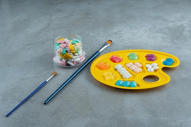 Stapel van verschillende kauwgom die op het palet wordt geplaatst.