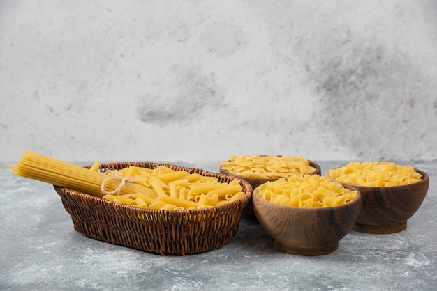 Stapel van verschillende ongekookte droge pasta in rieten mand en houten kommen.