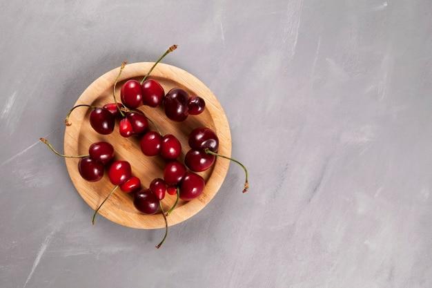 Stapel van verse dubbele kersenbessen (kersen) op een ronde houten dienende plaat.