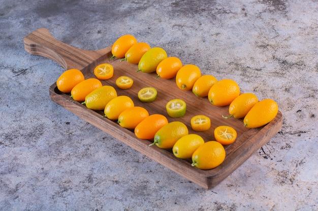 Stapel van verse kumquats op houten dienblad.