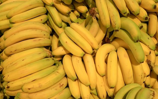 Stapel van verse rijpe bananen die in de markt verkopen