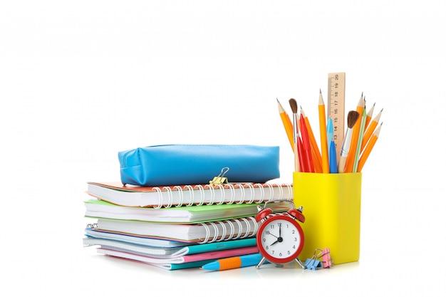 Stapel van voorbeeldenboeken en kantoorbehoeften die op wit worden geïsoleerd