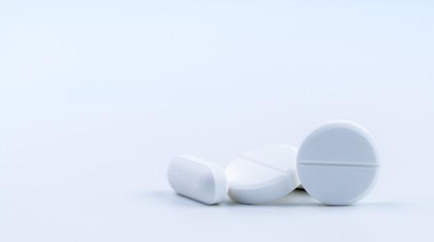 Stapel van witte ronde en langwerpige geïsoleerde tabletpillen