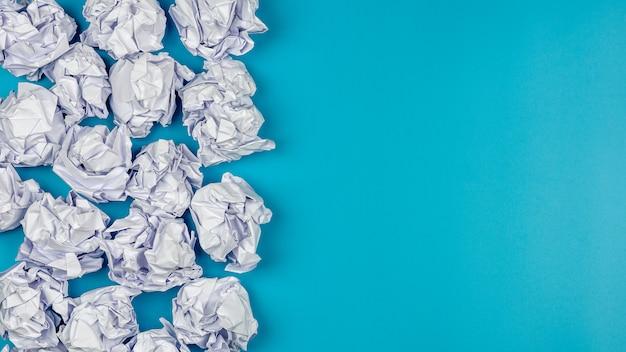 Stapel van witte verfrommelde document ballen op blauwe achtergrond.
