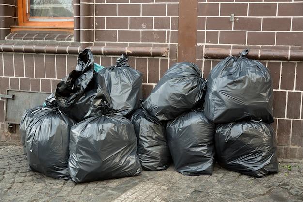 Stapel van zwarte vuilniszakken gevuld met afval in de buurt van bakstenen muur op straat