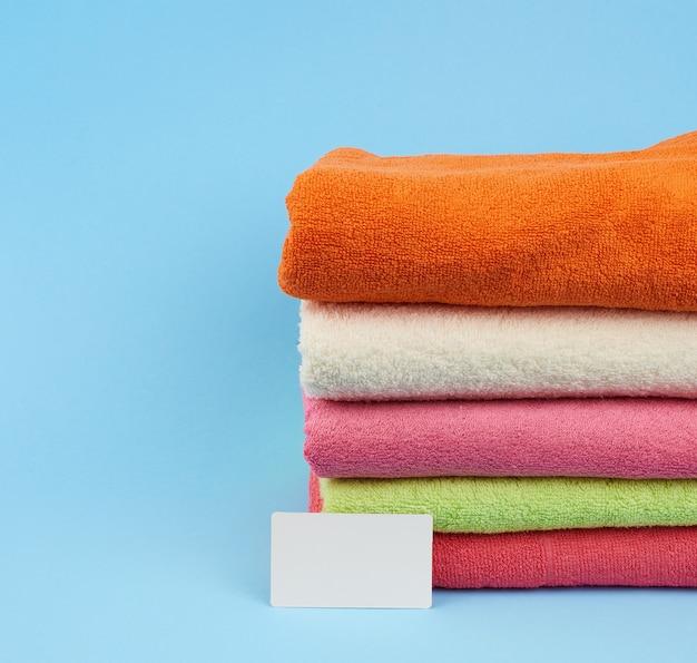 Stapel veelkleurige badstof handdoeken om het lichaam af te vegen na een douche en een wit blanco papier visitekaartje