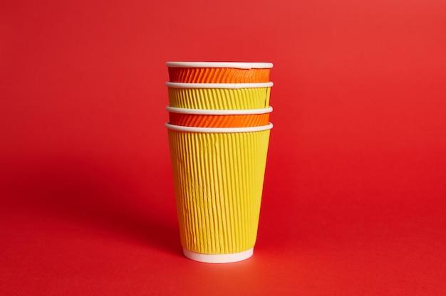 Stapel veelkleurige papieren wegwerpbekers voor warme dranken op een rode achtergrond met kopie ruimte.