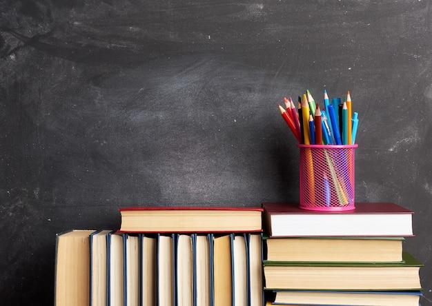 Stapel verschillende boeken, briefpapier op zwart krijtbord