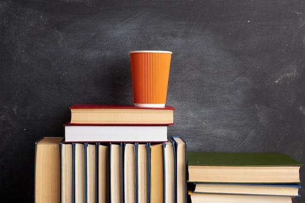 Stapel verschillende boeken en een oranje wegwerpbeker met koffie op een zwart krijtbord