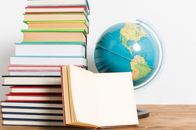 Stapel verschillende boeken en globe