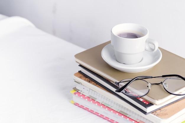 Stapel verschillende boeken en notitieblokken met vrouw glazen en koffiekopje op de top op een witte tafel.