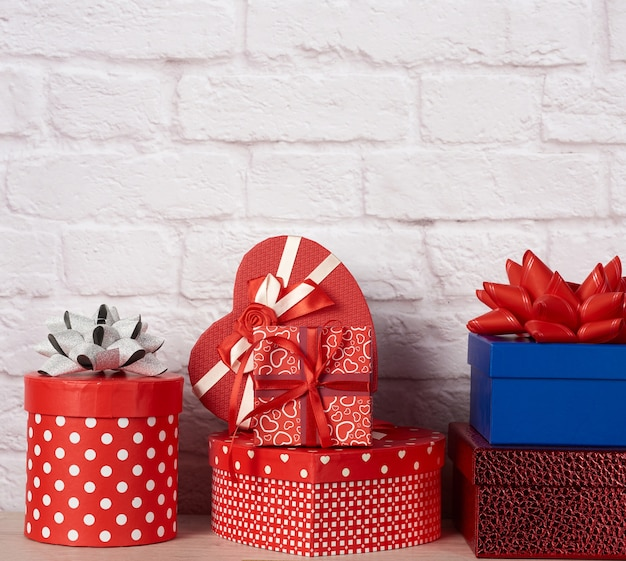 Stapel verschillende dozen met geschenken op witte bakstenen muur