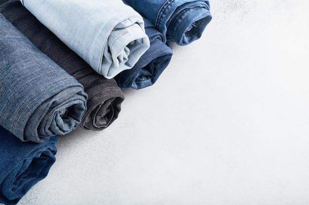 Stapel verschillende gerolde jeans op witte achtergrond