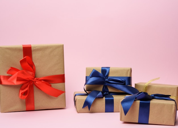 Stapel verschillende geschenkdozen op een roze achtergrond, feestelijke achtergrond