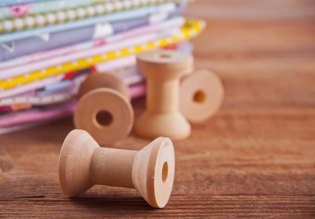 Stapel verschillende kleuren doek met lege houten draad spoelen