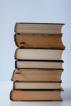 Stapel verschillende oude boeken op lichte achtergrond.