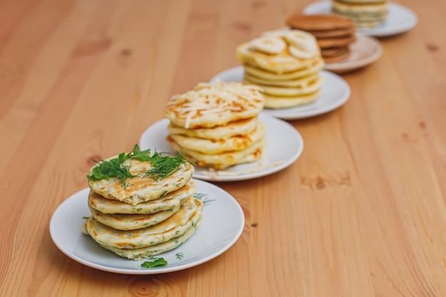 Stapel verschillende pannenkoeken op houten tafel
