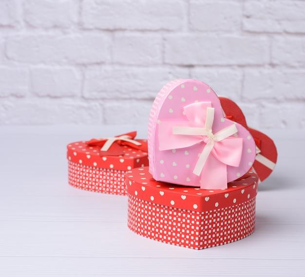 Stapel verschillende rode dozen met geschenken op witte achtergrond, feestelijke achtergrond