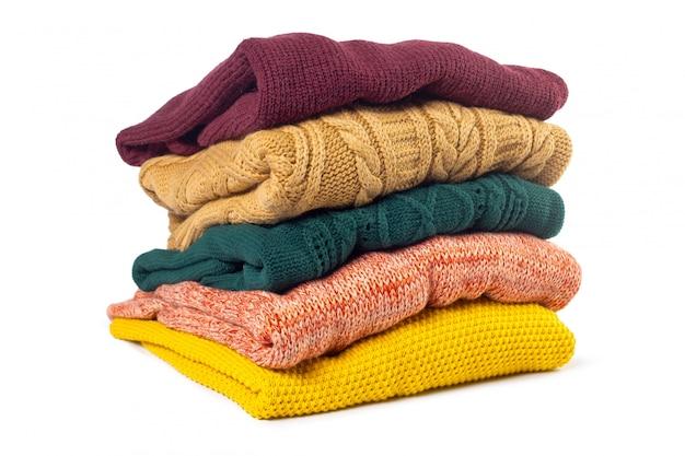 Stapel verschillende sweaters geïsoleerd op wit