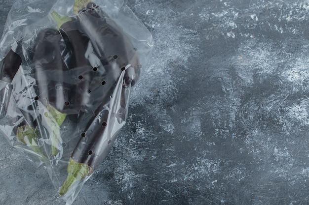 Stapel verse aubergines in plastic zak.