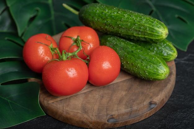 Stapel verse biologische groenten. komkommers en tomaten op een houten bord met groene bladeren.
