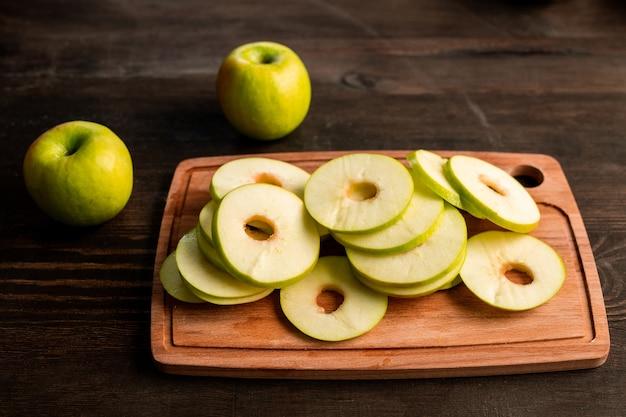 Stapel verse groene appels klaar om op fruit droger op houten snijplank te worden gezet en twee granny smiths in de buurt op keukentafel