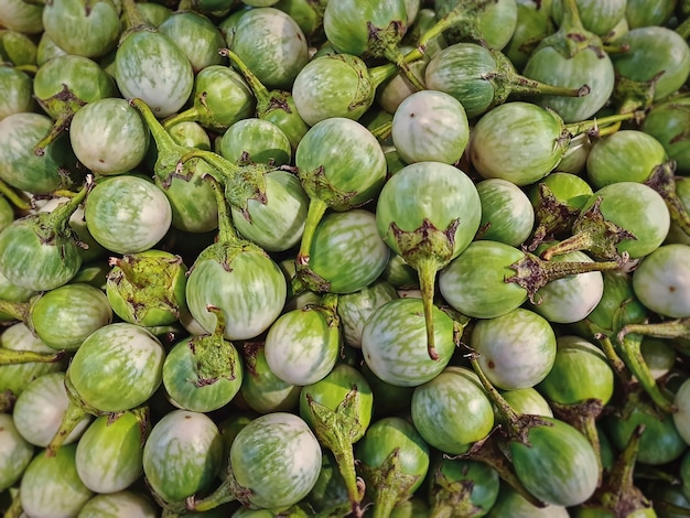 Stapel verse groene aubergines te koop bij marktkraam