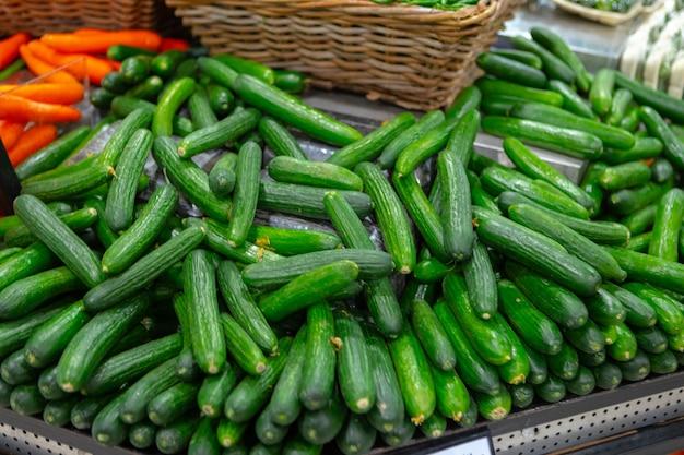 Stapel verse komkommers op teller in supermarkt