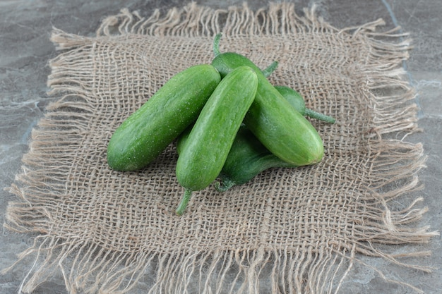 Stapel verse rijpe komkommer op zak over grijze tafel.