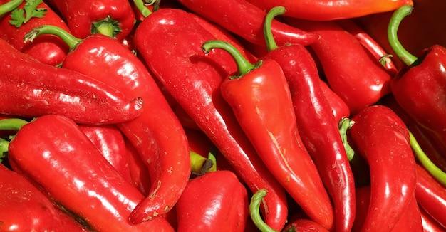 Stapel verse rijpe rode chilipepers te koop op de lokale markt