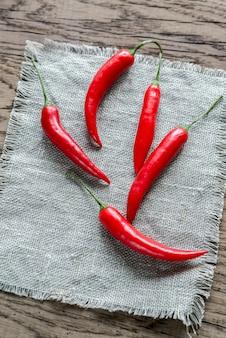 Stapel verse rode chili pepers op de jute