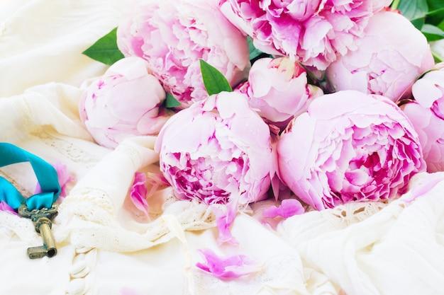 Stapel verse roze pioenroos bloemen op vintage kanten kledingstuk