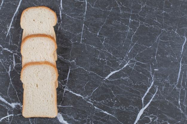 Stapel verse sneetjes brood op grijs.