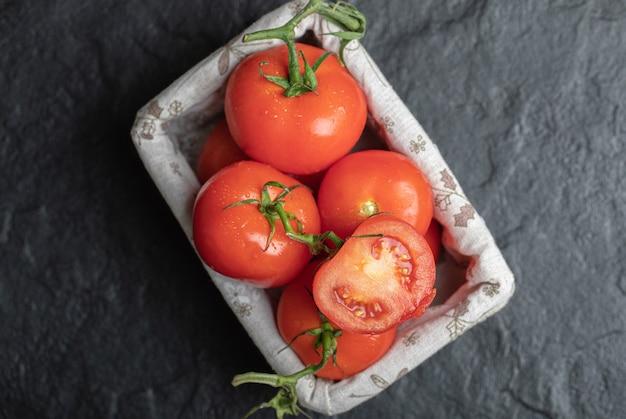 Stapel verse tomaten in mand op zwarte achtergrond.