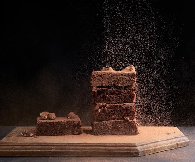 Stapel vierkant gebakken stukjes brownie besprenkeld met cacaopoeder, deeltjes bevroor in de lucht tegen een donker oppervlak