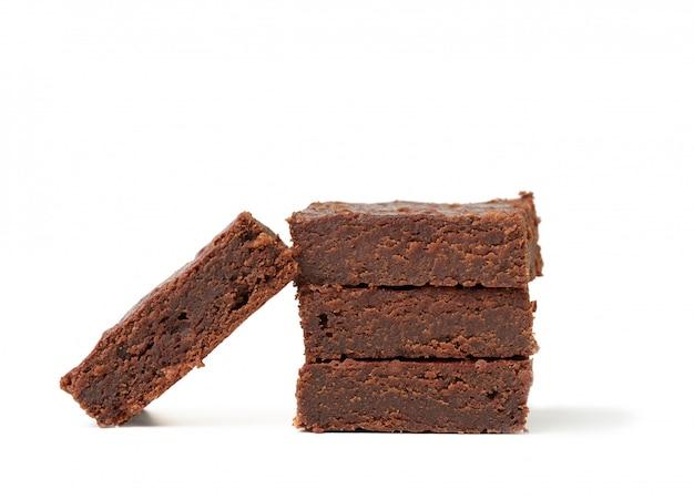 Stapel vierkant gebakken stukken van de cake van de browniechocolade die op een witte achtergrond, heerlijk dessert wordt geïsoleerd